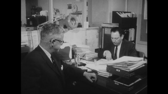 UNITED STATES: 1960s: men in office. Man on switchboard. Polic Officer talks to receptionsit