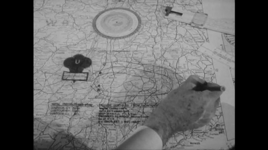 UNITED STATES: 1960s: hand makes notes on map. Men at desk. Poster on wall.