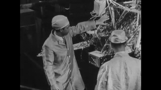 UNITED STATES: 1960s: engineer explains space capsule to man in lab