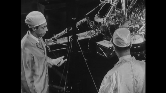 UNITED STATES: 1960s: scientist shows visitor around space module development. Hand points to component of space machine