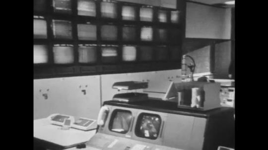 UNITED STATES: 1960s: two men walk through empty mission control. Monitors by desk. Man sits on desk. Men talk