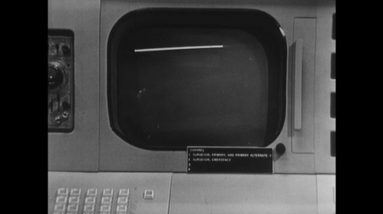 UNITED STATES: 1960s: close up of picture on screen. Men look at computers in base command for NASA