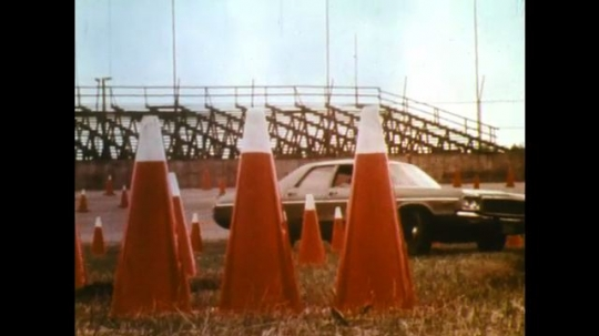 UNITED STATES: 1970s: car parks between cones on track. Drawing of race track. Man steers car.