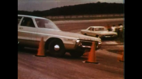 UNITED STATES: 1970s: car drives around cone course. Car parks between cones.