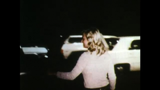 UNITED STATES: 1970s: lady gets into car. Car drives through cones.
