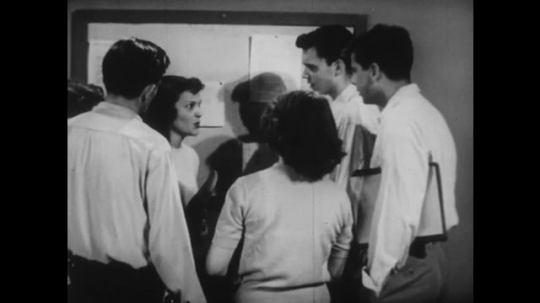 UNITED STATES: 1950s: teenagers talk in classroom. Students sit in audience.