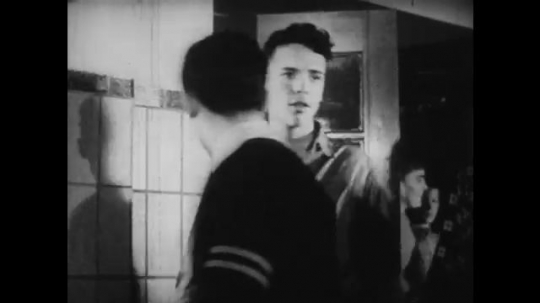 UNITED STATES: 1950s: students in school corridor. Boys talk in changing room.