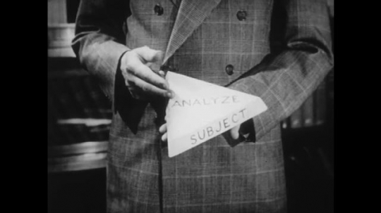 UNITED STATES: 1950s: man holds paper in hand. Man points to word