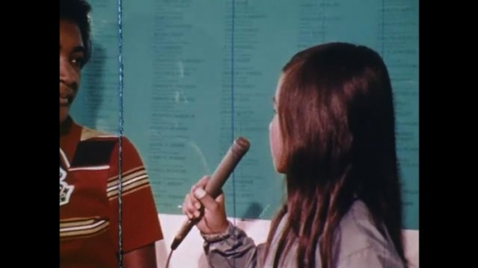 UNITED STATES: 1970s: girl interviews adults.