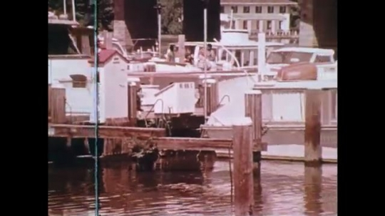 UNITED STATES: 1970s: children walk past boats in dock. Man looks through filing cabinet. Boy talks to camera.