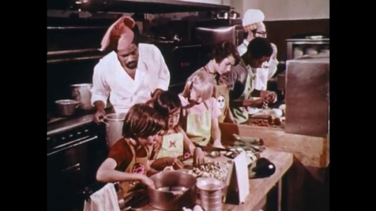 UNITED STATES: 1970s: children cook in kitchen with chef.