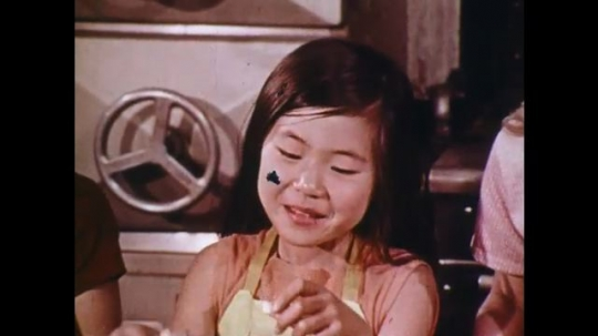 UNITED STATES: 1970s: girl prepares food in kitchen. Man cutting onions wipes eyes. Girl carries birthday cake. Children talk to camera