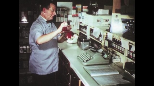 UNITED STATES: 1950s: pharmacist pours chemicals. Train moves along track slowly.