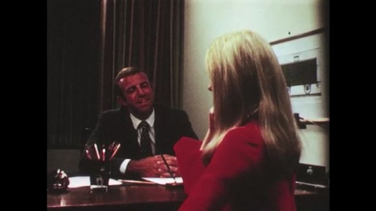 UNITED STATES: 1950s: man talks to lady at desk.