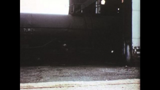 UNITED STATES: 1950s: train cars go into garage for inspection. Man drive train.