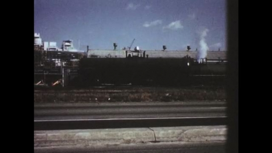 UNITED STATES: 1950s: train cars parked on tracks. Train on tracks in snow. Car on road.