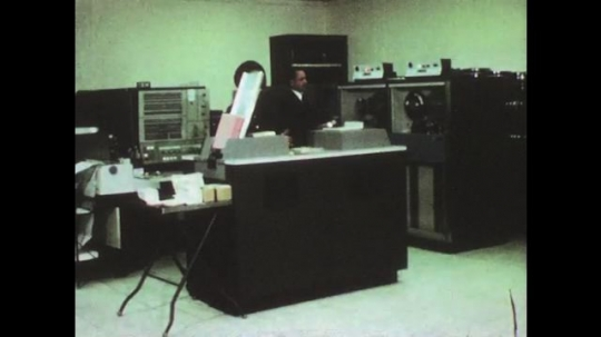 UNITED STATES: 1950s: people data process in office. Men on telephone. Dispatcher delivers materials to workmen in building.