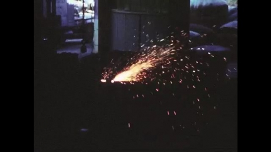 UNITED STATES: 1950s: sparks fly during welding process. Double bevel preparation in factory. Man works in factory.