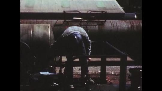 UNITED STATES: 1950s: man inspects train cart. Train carts on railway tracks. Lady talks to camera