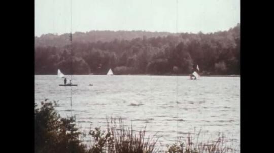 1970s: boats sail on lake. men run on beach toward ocean. pier stretches into water.