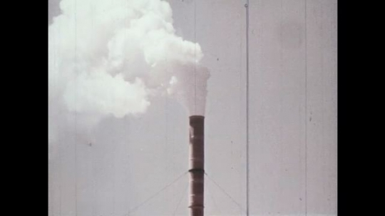 1970s: smoke rises from chimneys. trucks park at factory. factories pollute the air.