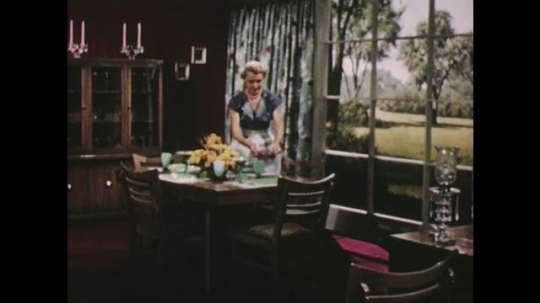 UNITED STATES: 1950s: lady lays table. Window in drawing room. Glass bottles.