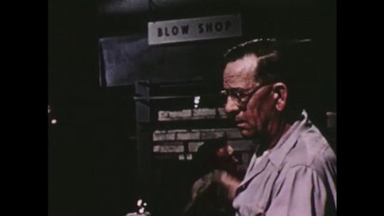 UNITED STATES: 1950s: glass blower uses blow mold. Mechanical production of glass.