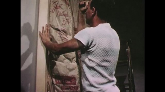 UNITED STATES: 1950s: man tacks glass blanket to wall in house. Insulation boards made from glass.