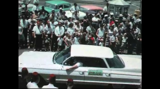 UNITED STATES: 1960s: cars in street parade. Marching band. Majorette throws baton.