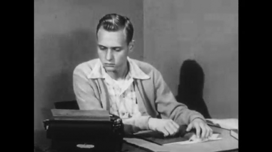 UNITED STATES: 1950s: boy looks at type writer. Boy looks at book