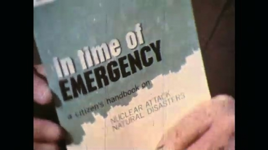 UNITED STATES: 1970s: 'in time of emergency' book cover. Man reads book. Fallout shelter pictures in book.