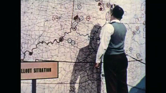 UNITED STATES: 1970s: man at office draws on wall map. Man speaks on phone in booth. Workers at civil defense building.