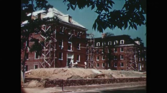 1950s: men work on construction of large academic buildings. cars drive down franklin street. men stand outside post office. church with steeple.