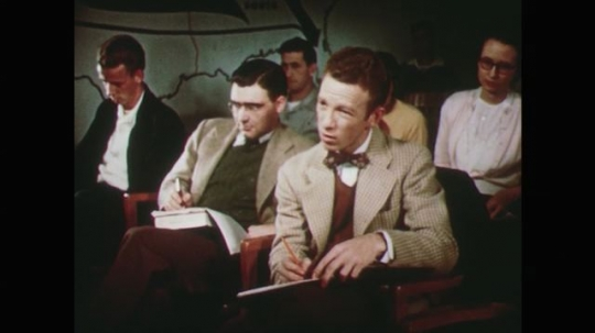 1950s: men and women sit at desks and write notes. hand writes in notebook with pen.