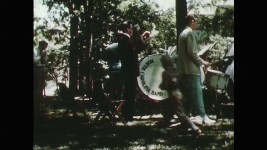 1950s: men play drums in park. men and women shake hands. men in navy uniform talk to woman. man sits on bench and reads newspaper.