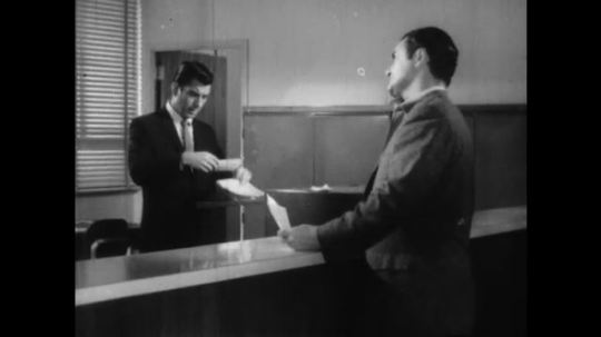 UNITED STATES: 1960s: two men at information desk. Man asks question. Man looks at paper.