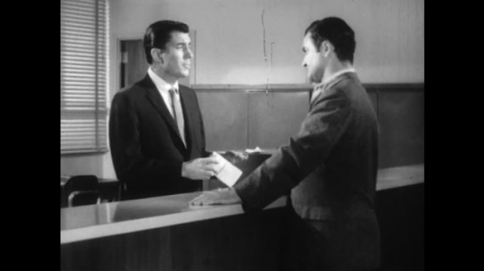 UNITED STATES: 1960s: two men speak at desk. Man looks at paper.