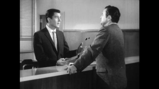 UNITED STATES: 1960s: two men speak at desk. Close up of man speaking.
