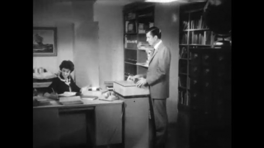 UNITED STATES: 1960s: man speaks to lady at desk. Man looks at watch. Man and lady annoyed in conversation
