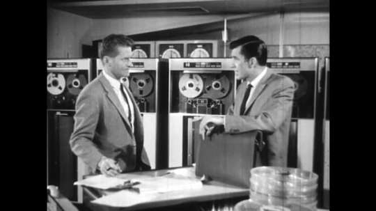 UNITED STATES: 1960s: men meet in computer room and talk. Close up of man