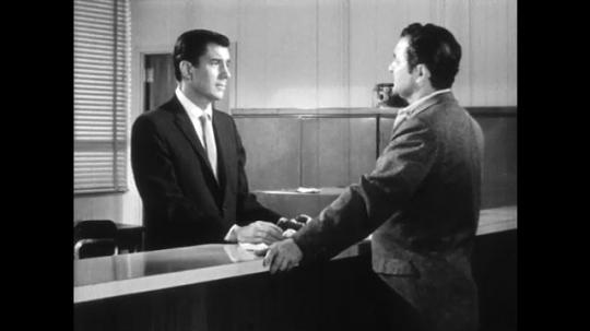 UNITED STATES: 1960s: two men speak at reception desk.