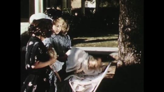 UNITED STATES: 1950s: girls play with dolls in garden. Boy runs to tree. Boy hides behind tree