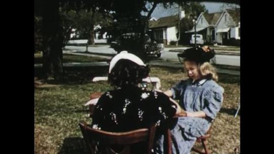 UNITED STATES: 1950s: girls have pretend tea in garden. Boy hides from girls. Boy grins. Crayola crayons.