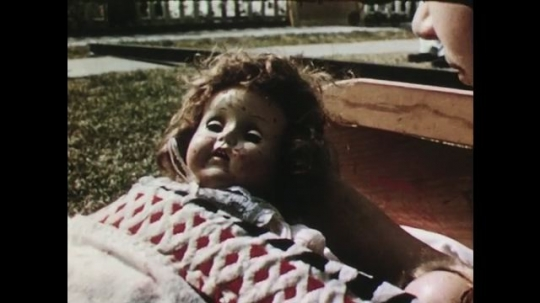 UNITED STATES: 1950s: doll with crayon on face. Girl finds doll with crayon on face. Girls talk to lady. Lady calls children home