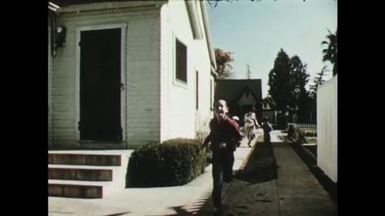 UNITED STATES: 1950s: boy runs to camera. Children run through garden with lady. Washing on line