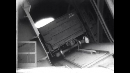 1950s: United States: ore cars turned upside down in dumping machine. Ore falls into hopper. Ore on conveyor belt