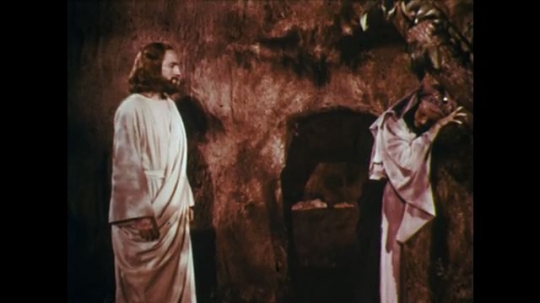 UNITED STATES: 1950s: lady cries in cave. Jesus stands behind lady. Jesus arises from dead.