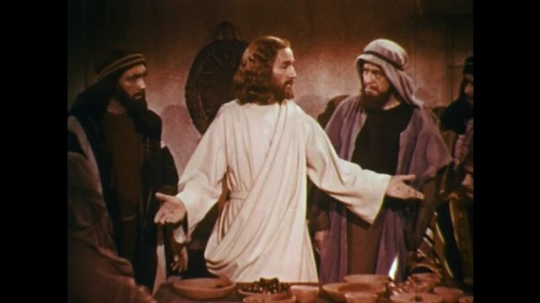 UNITED STATES: 1950s: Jesus meets with men at table. Jesus breaks bread. Man eats bread at table