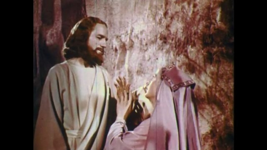UNITED STATES: 1950s: woman kneels at feet of Jesus by tomb entrance. Jesus speaks to lady.