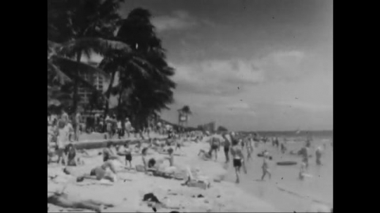 UNITED STATES: 1960s: people on crowded beach. Child plays in sand. Surfers catch waves